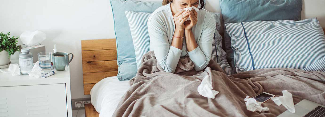Une femme se mouche le nez dans son lit avec un mouchoir