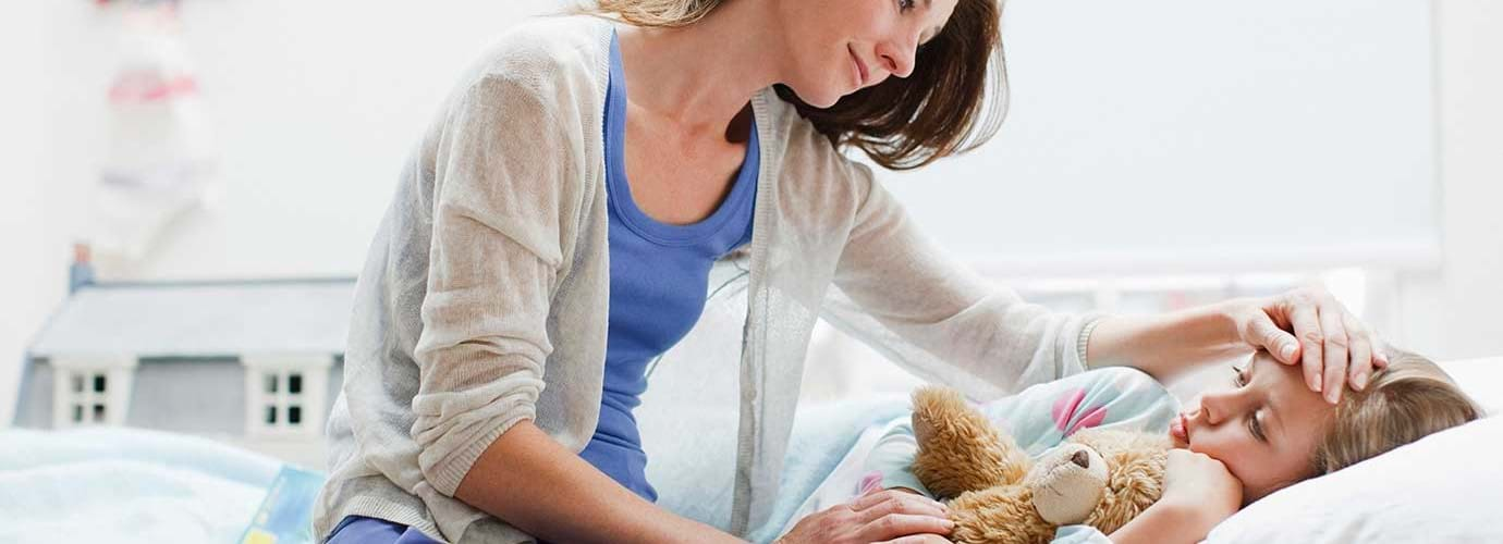 Une mère s'occupe de sa fille dans son lit avec un rhume