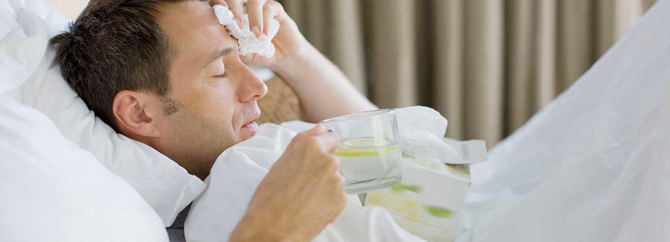 Un homme malade dans son lit tient une tasse de thé au citron et des mouchoirs