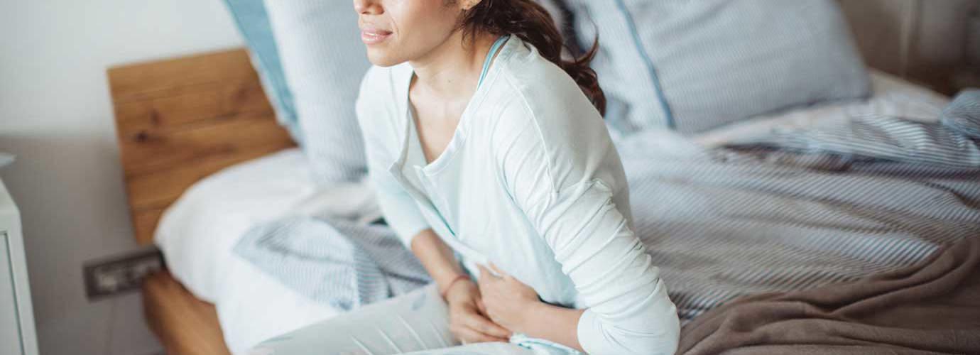 Nainen istuu sängyllä vatsakivuista kärsien