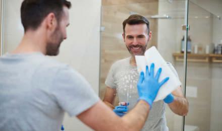 Sinisiin suojakäsineisiin sonnustautunut nainen puhdistaa kylpyhuoneen peiliä
