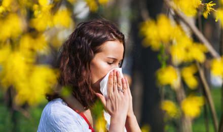Nuori nainen aivastaa nenäliinaan pellolla, jolla kasvaa suuri määrä luonnonvaraisia kukkia, joissa on runsaasti siitepölyä