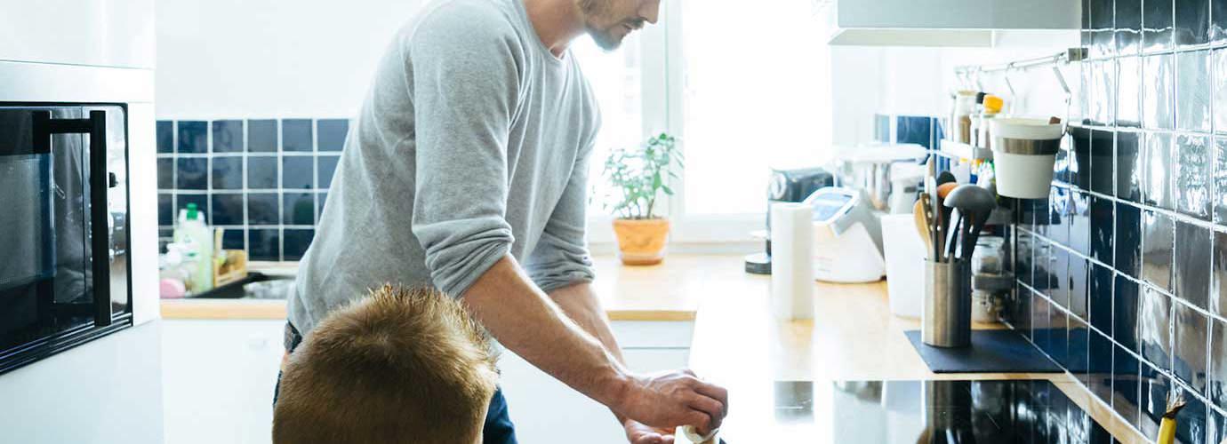 Mies puhdistaa keittiötasoa lapsen katsoessa tarkasti vierestä