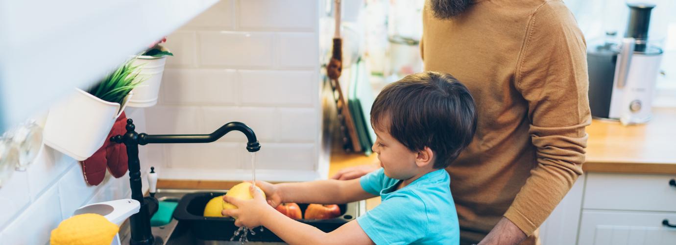 Äiti auttaa lapsiaan pesemään kädet keittiössä