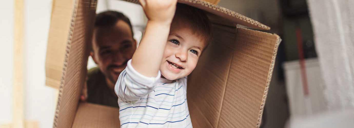 Un petit garçon tient une boîte en carton pendant un déménagement avec sa famille