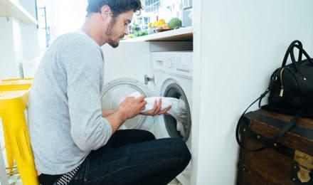 Mies laittaa vaatteita pesukoneeseen