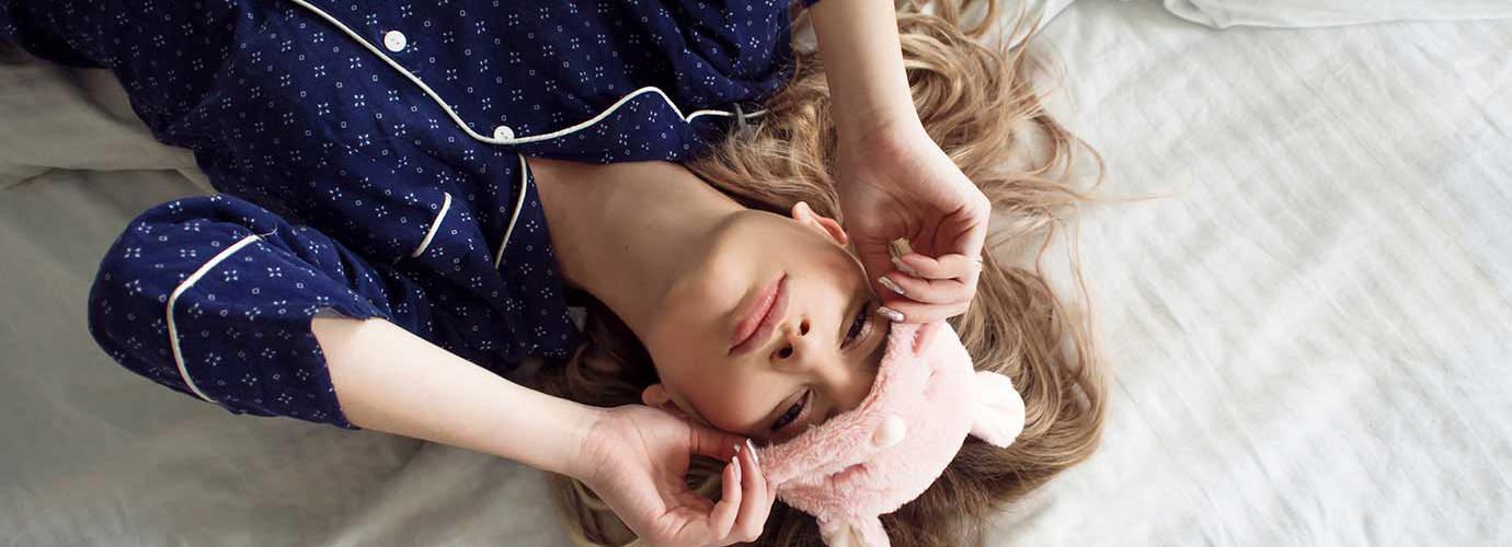 Silmäsuojaa käyttävä lapsi makaa yöllä sängyssä nenä tukkoisena