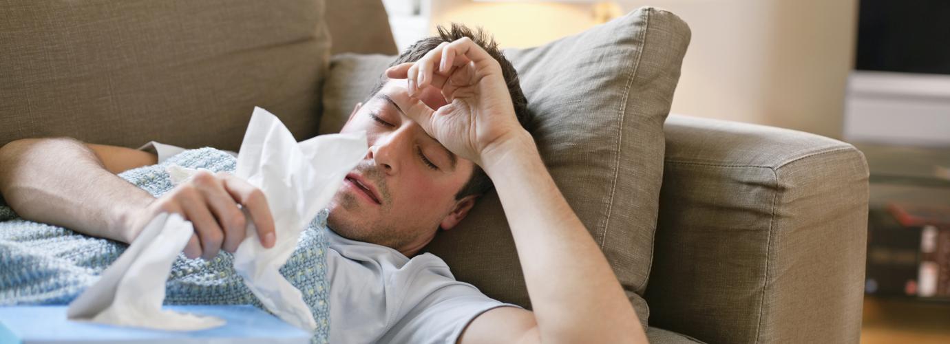 Mies makaa sohvalla miesflunssassa pidellen käsissään nenäliinoja