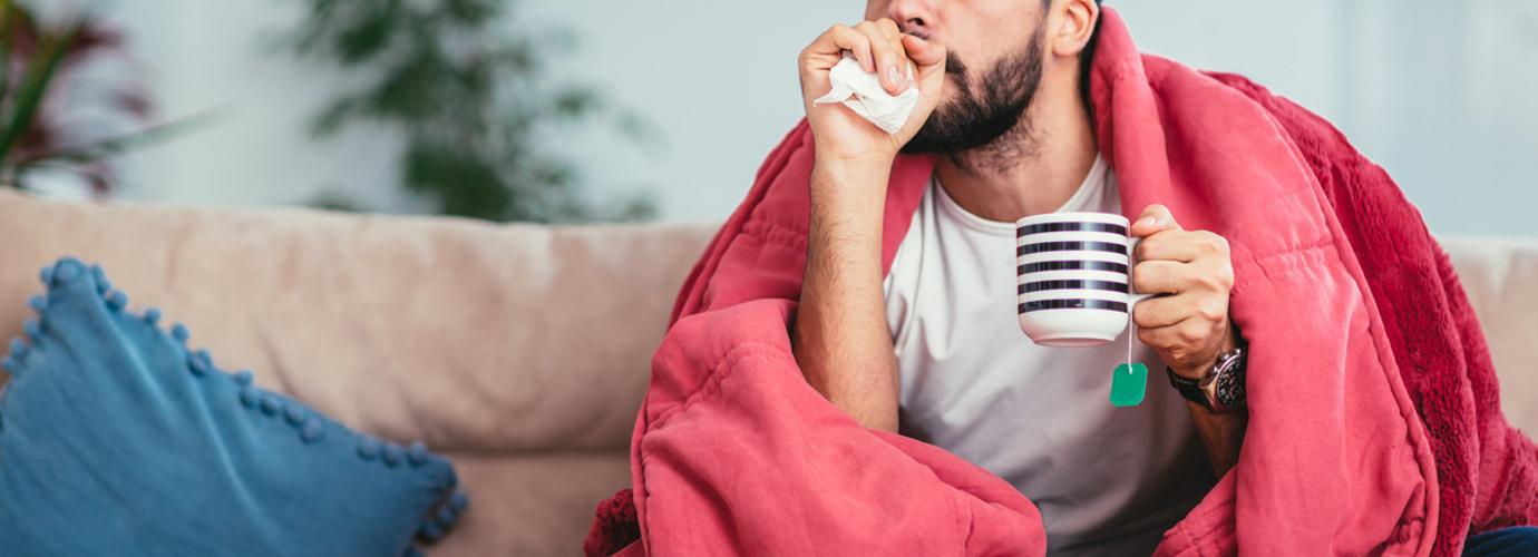Nuori mies yskii sohvalla peiton alla kädessään teemuki ja nenäliinoja