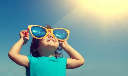 Un jeune enfant avec une paire de lunettes de soleil surdimensionnées et comiques fait le plein de vitamine D grâce au soleil dans le ciel