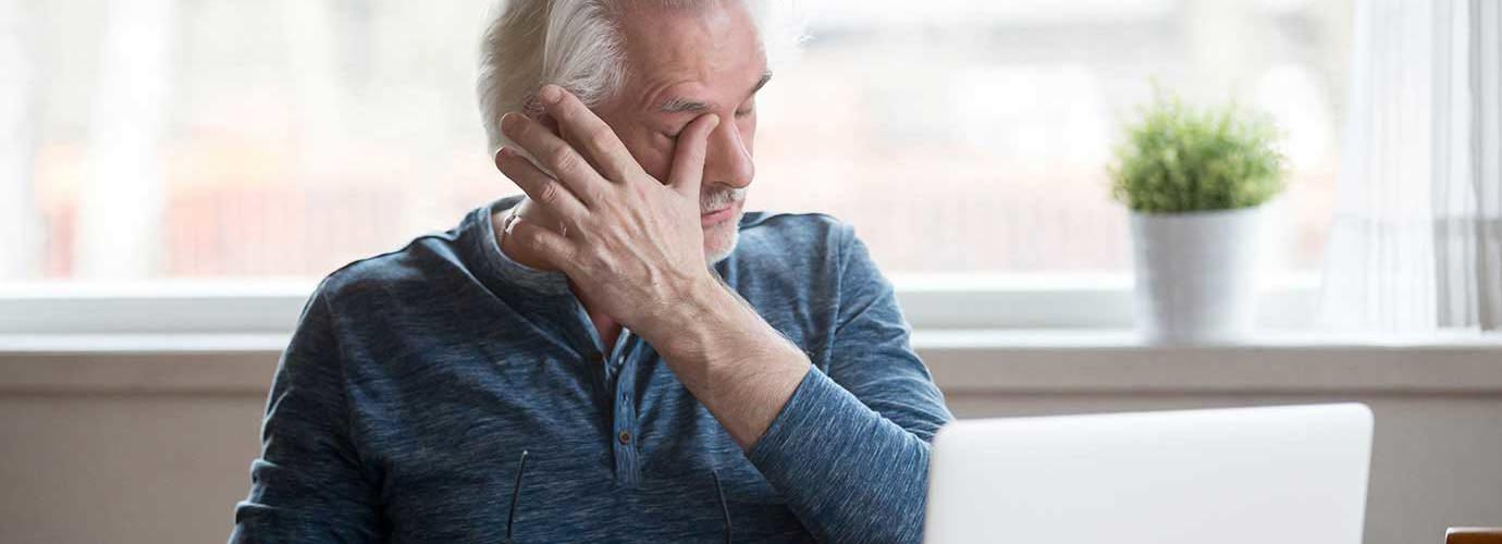 Un homme âgé devant un ordinateur portable a des démangeaisons dans l'oeil