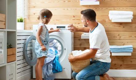 Père et fille font la lessive ensemble et passent un moment amusant
