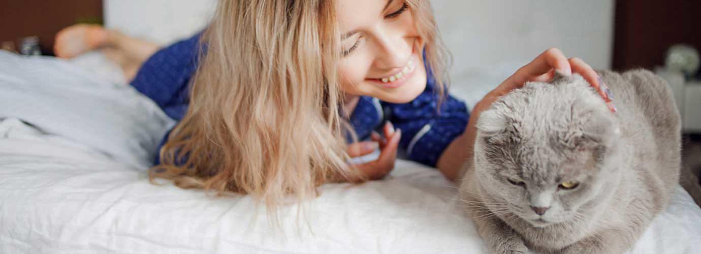 Une femme allongée sur son lit, caresse son chat, elle ne présente pas clairement les symptômes d'allergie aux poils de chat